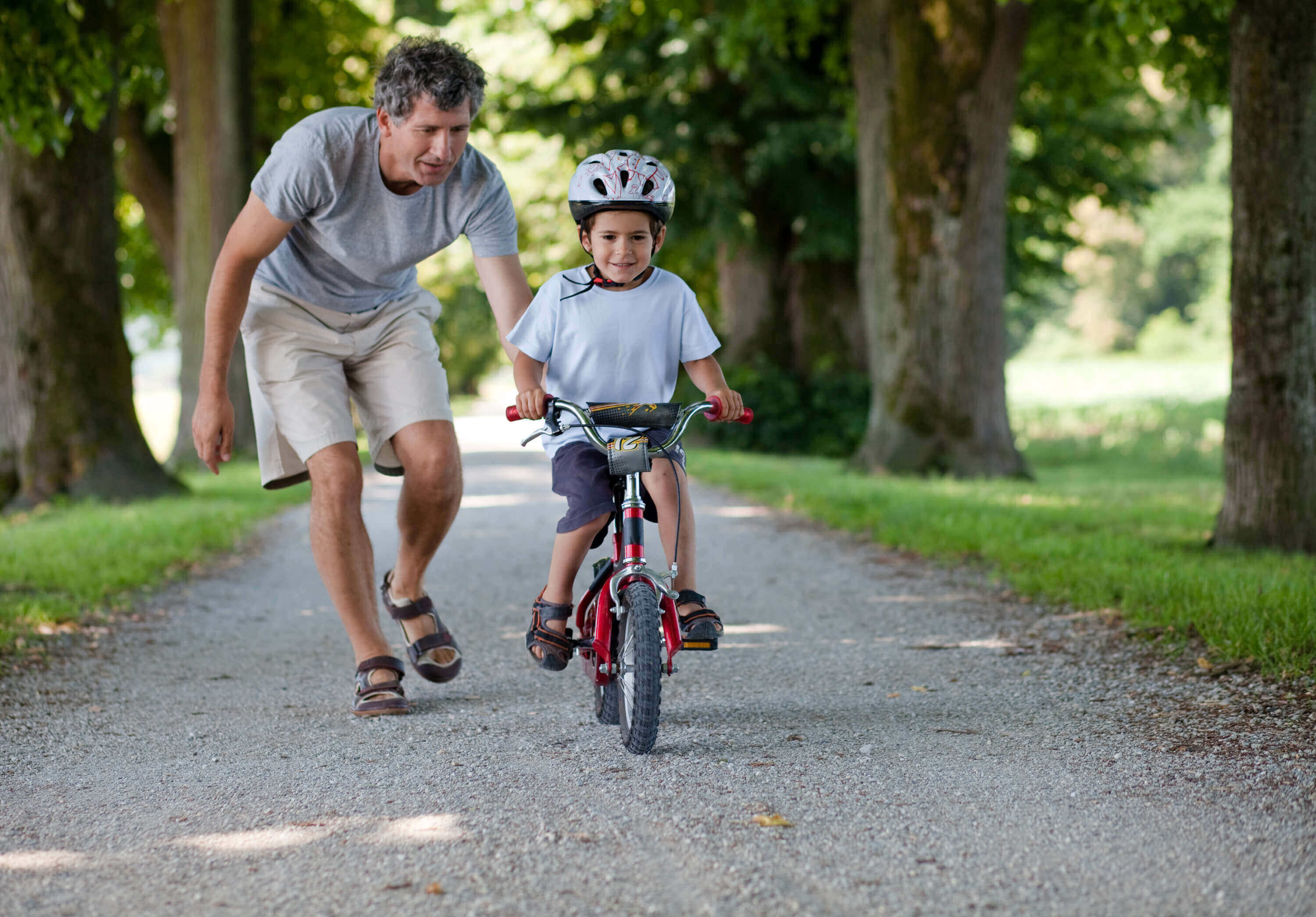 Child riding a bike, while father guides him